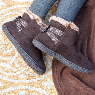 Women's Microsuede Addie Boot Slippers with Bow in Dark Chocolate on Model laying on rug and brown blanket showing off the bow-ribbon detailing