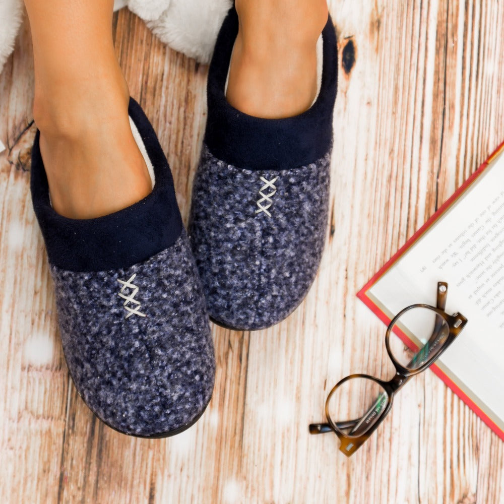 Women's Heathered Knit Jessie Hoodback Slippers in Navy Blue on Model reading  on hardwood floor