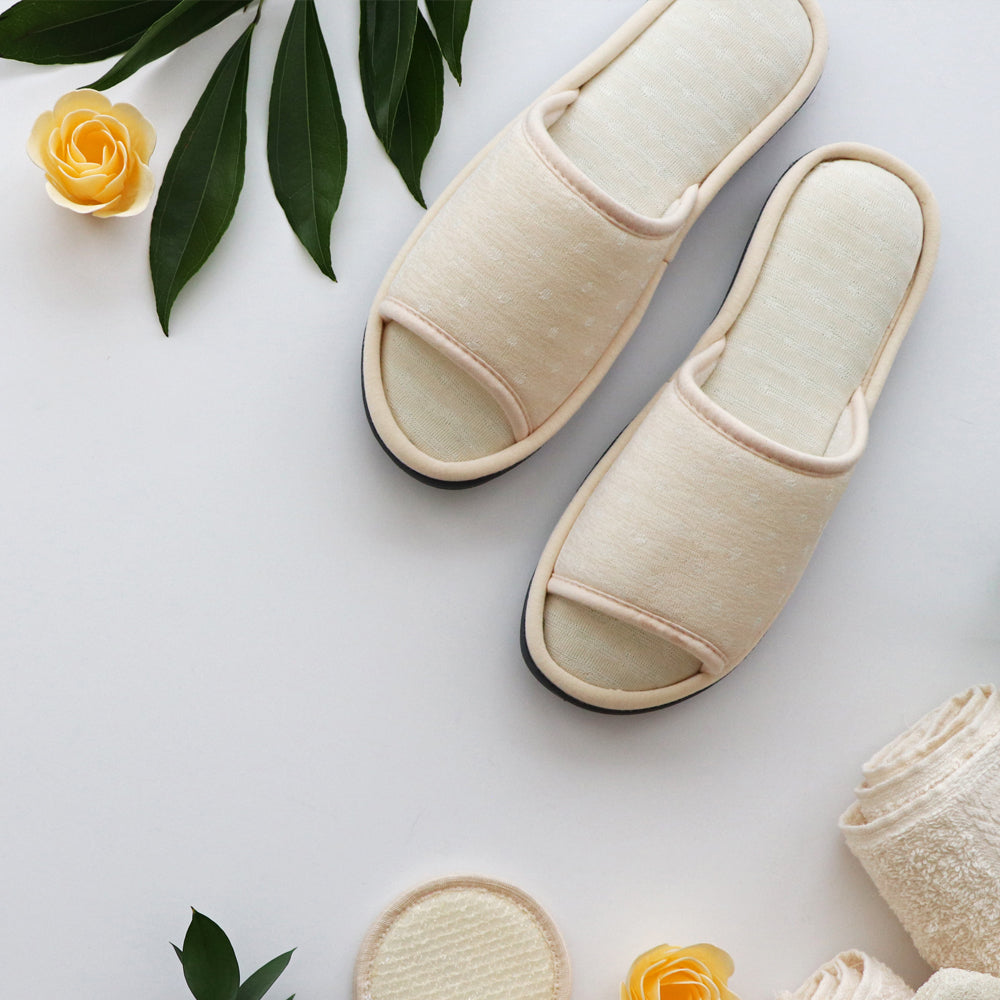 Women's Jersey Ada Slide Slipper in Sand Trap (Beige) flatlay with greenery, flowers and towels on white background