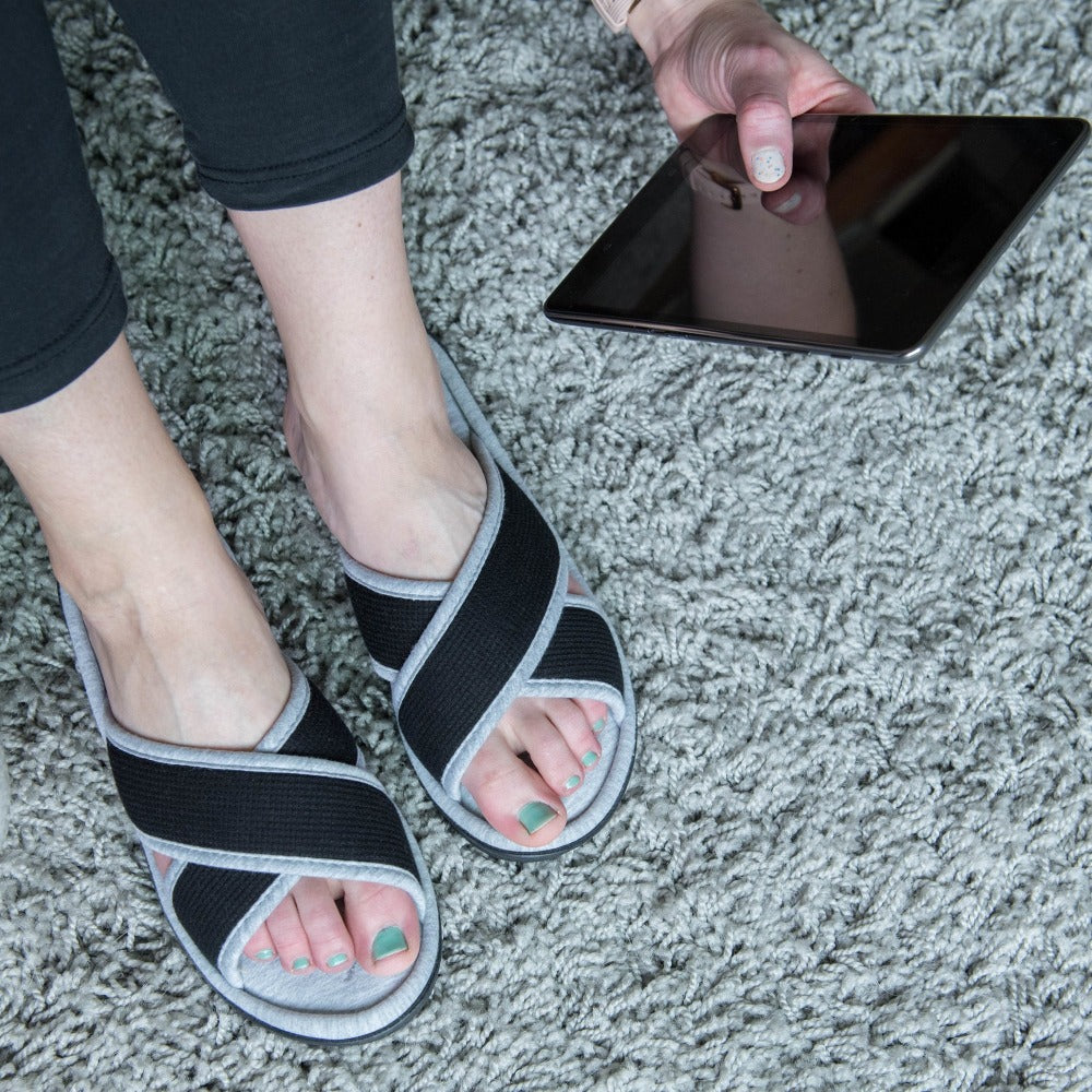 Women's Waffle Knit Helena X-Slide Slipper in Black on Model sitting on a shag rug looking at a tablet
