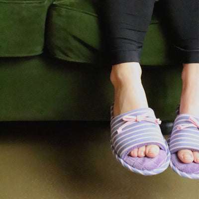 Women's Nani Stripe Slide Slippers in Iris (Purple) on Model sitting on green couch with her feet dangling
