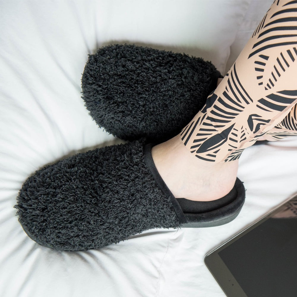 Women's Chenille Parker Clog Slippers in Black on model in bed with a tablet