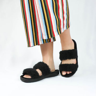 Women's Chenille Parker 2-Band Slide Slippers in Black on Model standing on white backdrop with fun striped pants on