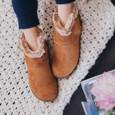 Women's Microsuede Mallory Bootie with Bow Slippers in Cognac Brown sitting on a couch with a crotchet blanket