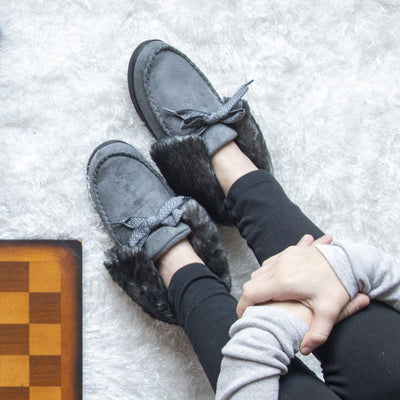 Women's Microsuede Nelly Moc Bootie Slippers in Ash on figure. Female model wearing slippers while holding her knees next to a checkers board