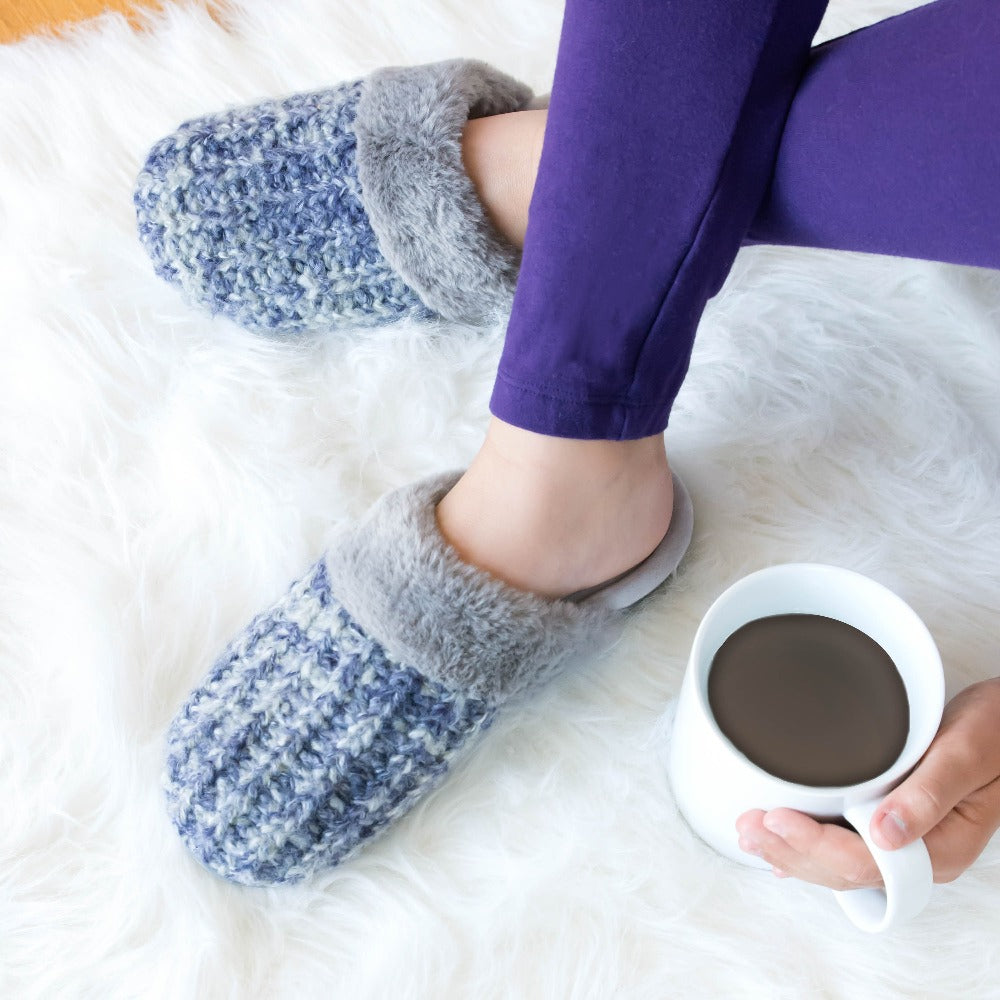 Women's Sweater Knit Shelia Clog Slippers in Navy Blue on figure, model relaxing on a plush faux fur blanket with a cup of coffee