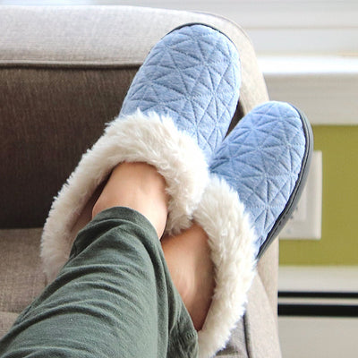 Women's Recycled Quilted Bridget Hoodback Slippers in Blue Marlin on figure. Model's feet sitting on a the edge of a couch