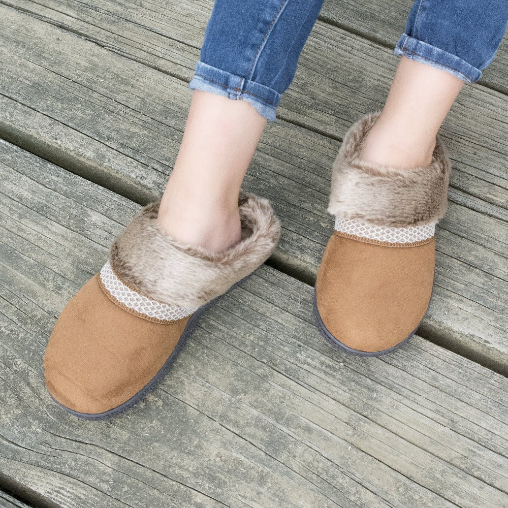 Women's Recycled Microsuede Mallory Hoodback Slippers in Cognac Tan on model sitting on a weathered bridge, top down view of the slippers