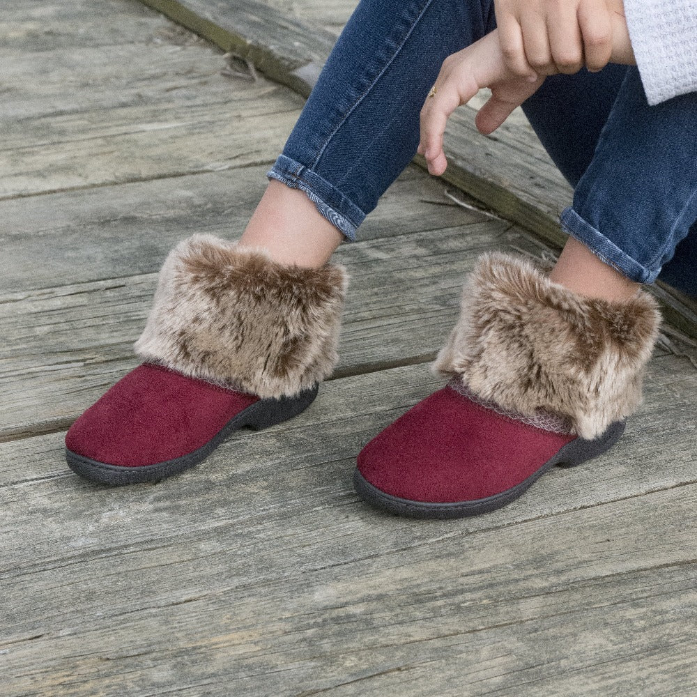 Women's Recycled Microsuede Mallory Boot Slippers in Chili Red on figure sitting on a wood bridge with her arms draped over her knees