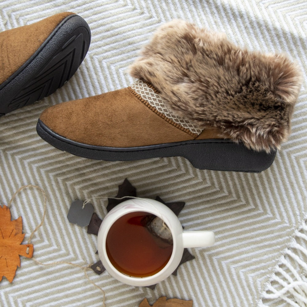 Women's Recycled Microsuede Mallory Boot Slippers in Cognac Tan flatlay on top of striped blanket and a cup of tea