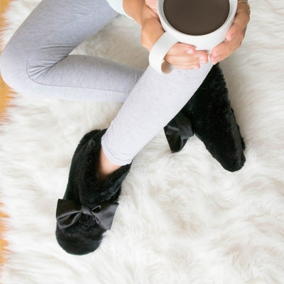 Women's Fur and Satin Tabby Boot Slippers in Black on figure model sitting on comfy faux fur blanket with her legs crossed and a cup of coffee resting on her knee