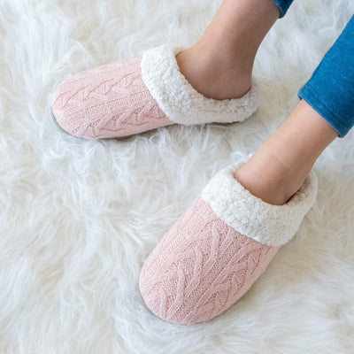 Women's Cable Knit Alexis Hoodback Slippers in Evening Sand Pink sitting on a comfy white faux fur blanket