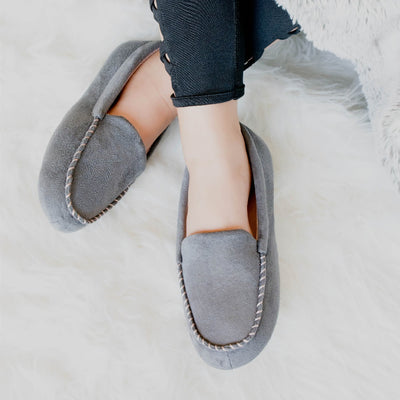 Women's Microsuede Noela Moccasin Slippers in Ash on model laying on a fluffy white rug with her legs crossed at the ankles