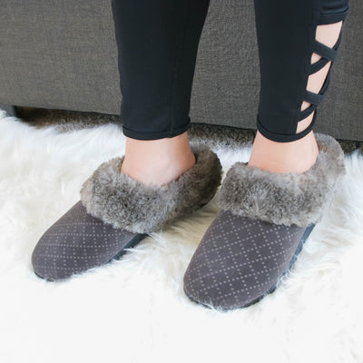 Women's Velour Sabrine Hoodback Slippers in Mineral on figure sitting on a couch with her feet on a fluffy rug