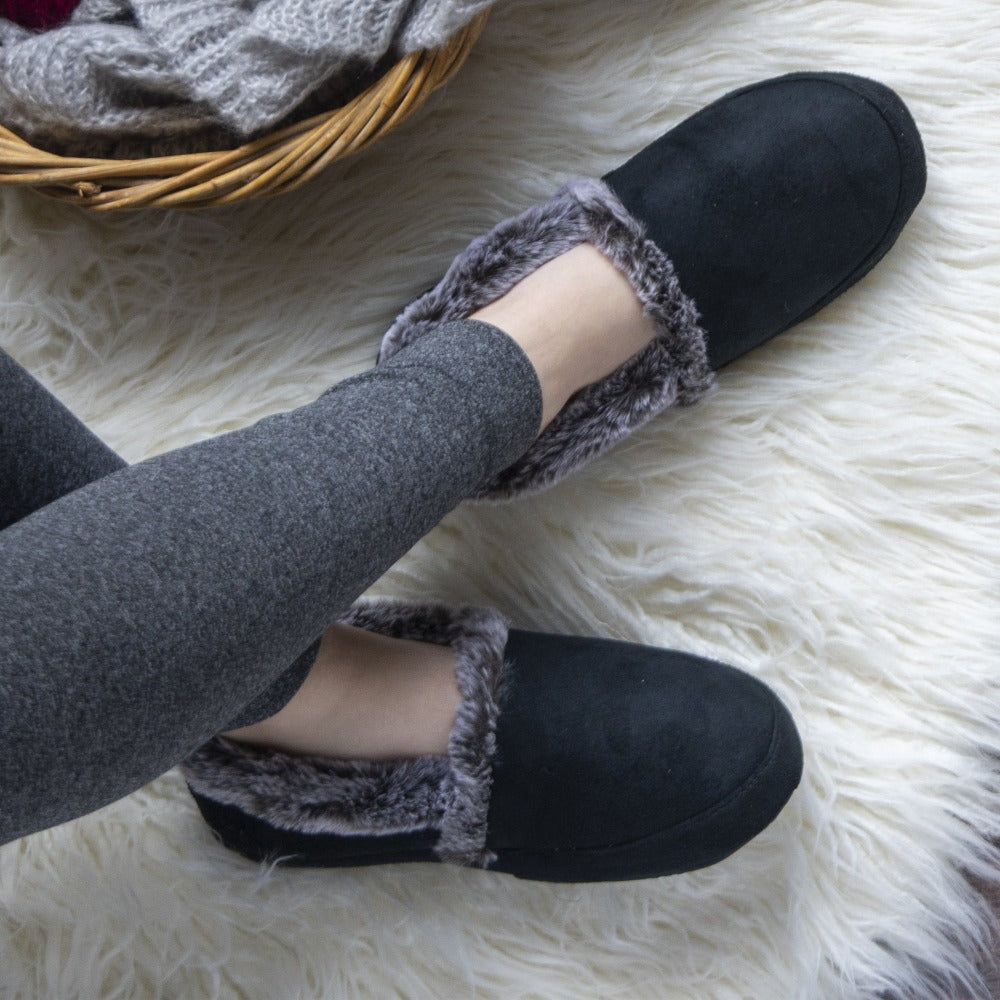 Women's Recycled Microsuede A Line Slippers in Black on figure. Model sitting on a fluffy in rug in her slippers next to a basket of knitting supplies
