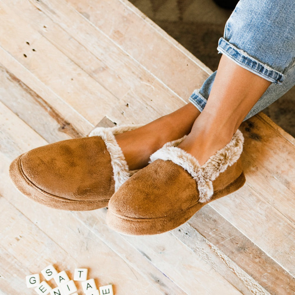 Women's Recycled Microsuede A Line Slippers in Cognac on figure. Model's feet are sitting on top of a coffee table next the letter titles