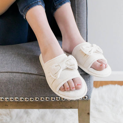 Women's Recycled Woven Petunia Slide Slipper in Ewe on figure. Model sitting in chair with her slippered feet on the side of the chair. Her hands hugging her knees.