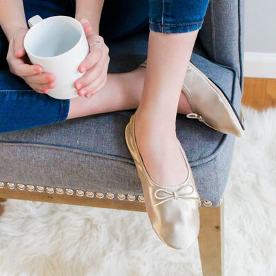 Women's Sloan Printed Ballerina Slippers in Sandtrap on figure. Model sitting with her feet crossed on the edge of a chair with a cup of coffee in her hand