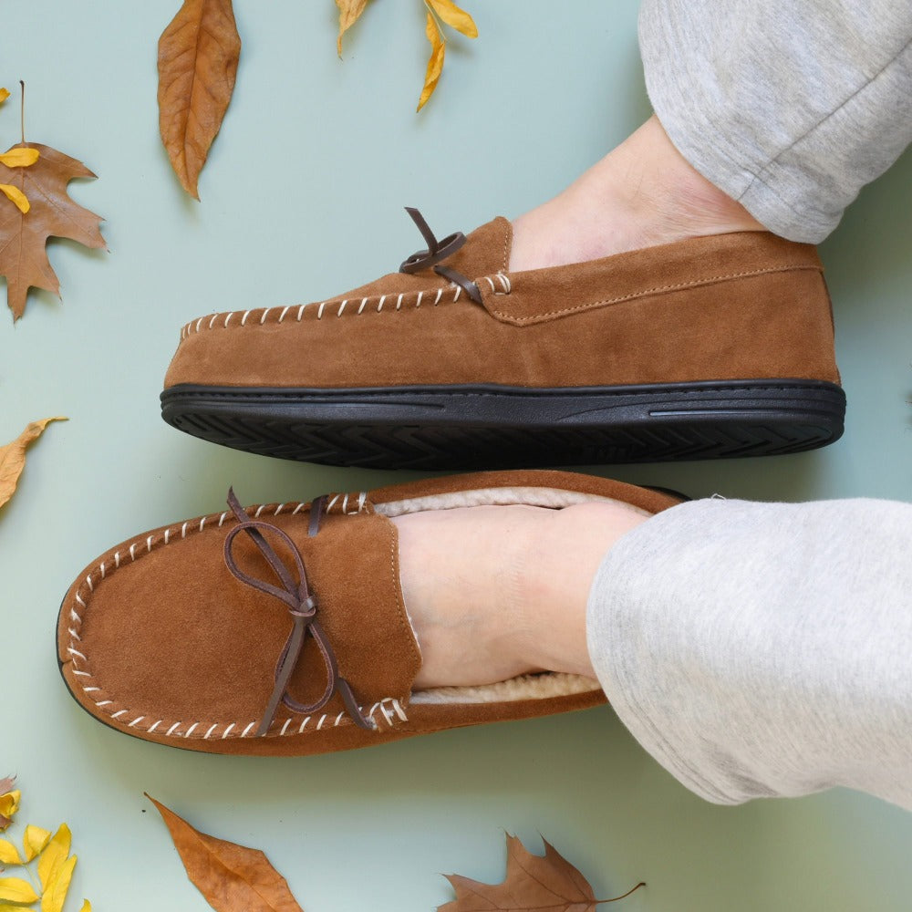 Men's Genuine Suede Moccasin Slippers in Buckskin on figure. Male model's slippered feet sit on a blue background with leaves around them