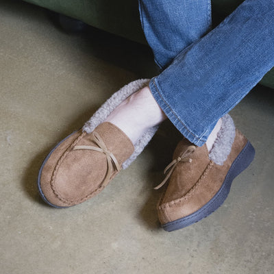 Men's Microsuede Moccasin Slippers in Cognac Tan on figure with his feet crossed at the ankles