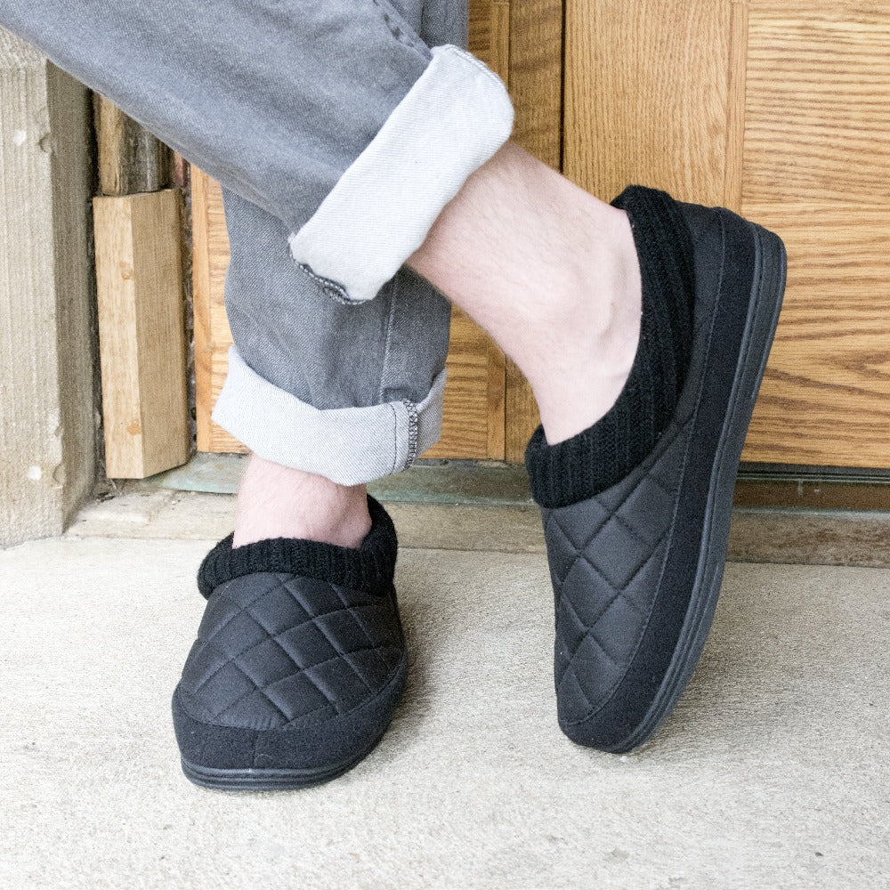 Men's Quilted Levon Low Boot Slippers in Black on figure standing in front of wooden door with one foot crossed over the other