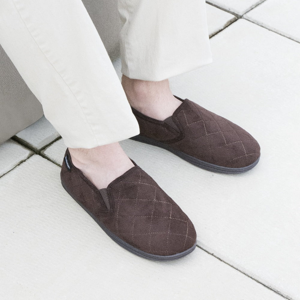 Men's Quilted Nicco Closed Back Slippers in Dark Chocolate on figure sitting on beanbag with feet on tile