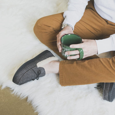 Men's Plaid Tanner Moccasin Slipper in Smokey Taupe with model sitting with his legs crossed with a cup of coffee on a plush rug