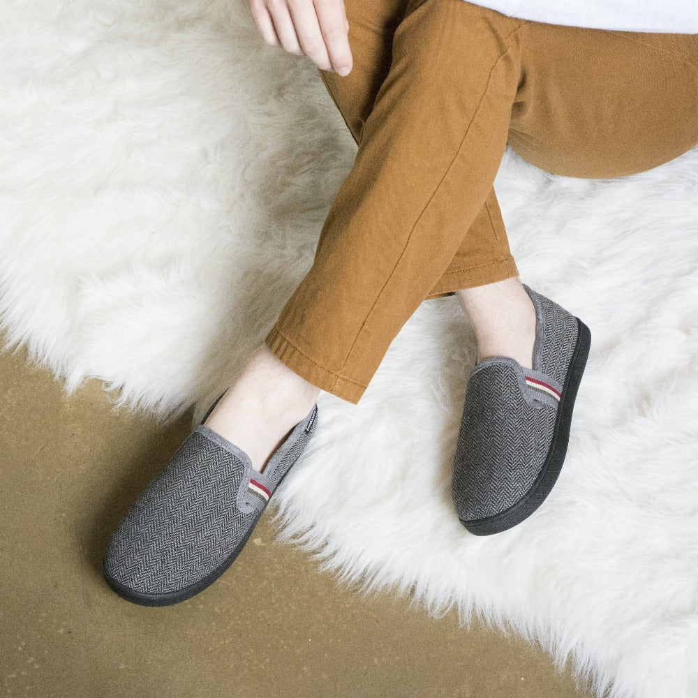 Men's Herringbone Maverick Closed Back Slippers in Black on figure, model sitting on a plush rug with their hands draped over his knees, ankles crossed