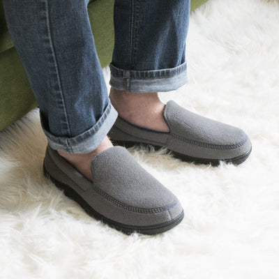 Men's Recycled Fleece Roman Moccasin Slippers in Ash on figure sitting on a couch with the models feet on a fluffy rug