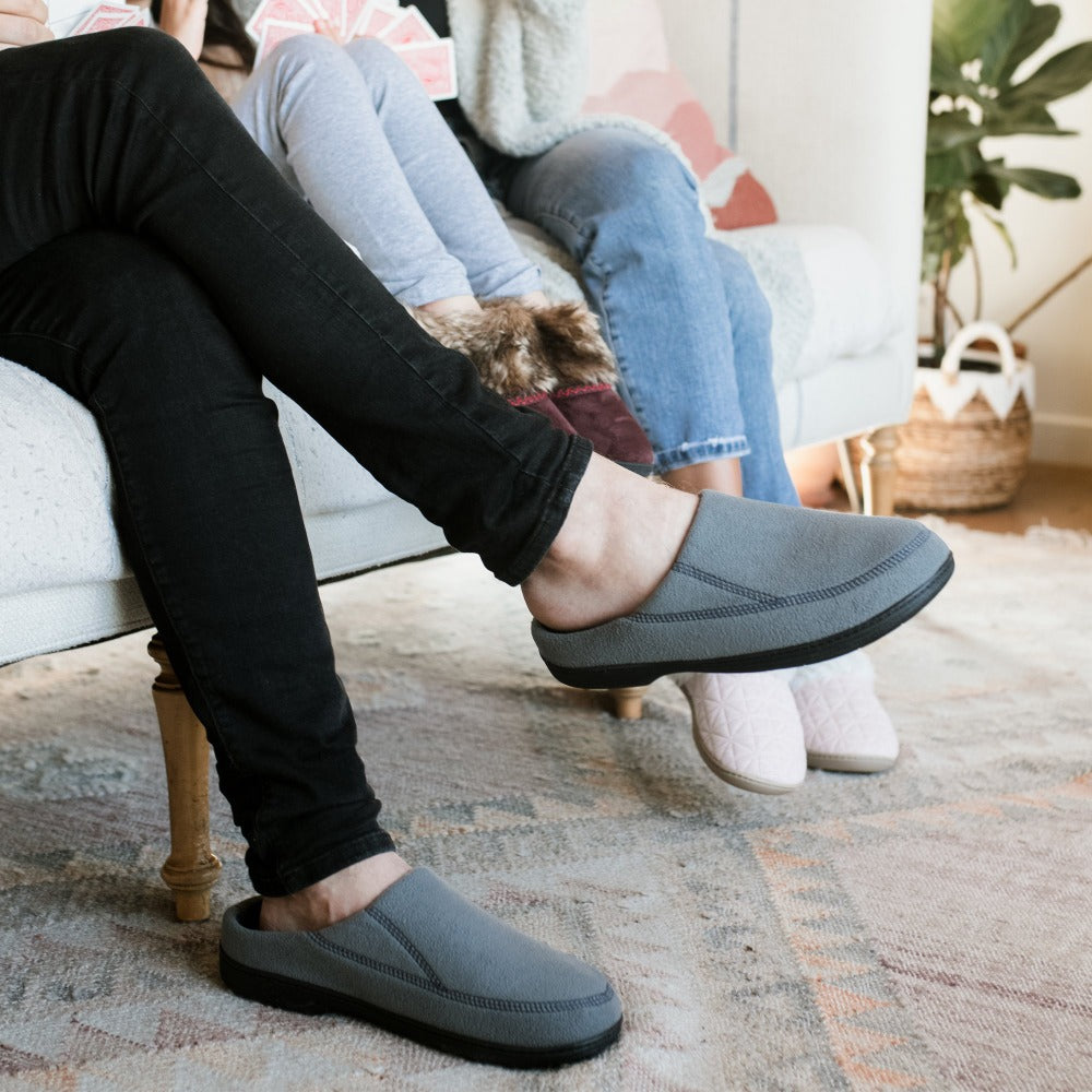 Men's Recycled Fleece Roman Hoodback Slippers in Ash on figure. Male from the knee down sitting on couch with his legs crossed wearing slippers while daughter and wife sit next to him