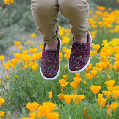 Woman jumping in a field of poppy flowers wearing the zenz balance slip on