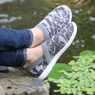 Woman wearing Zenz Harmony Slip on in Geo Print resting feet on a rock