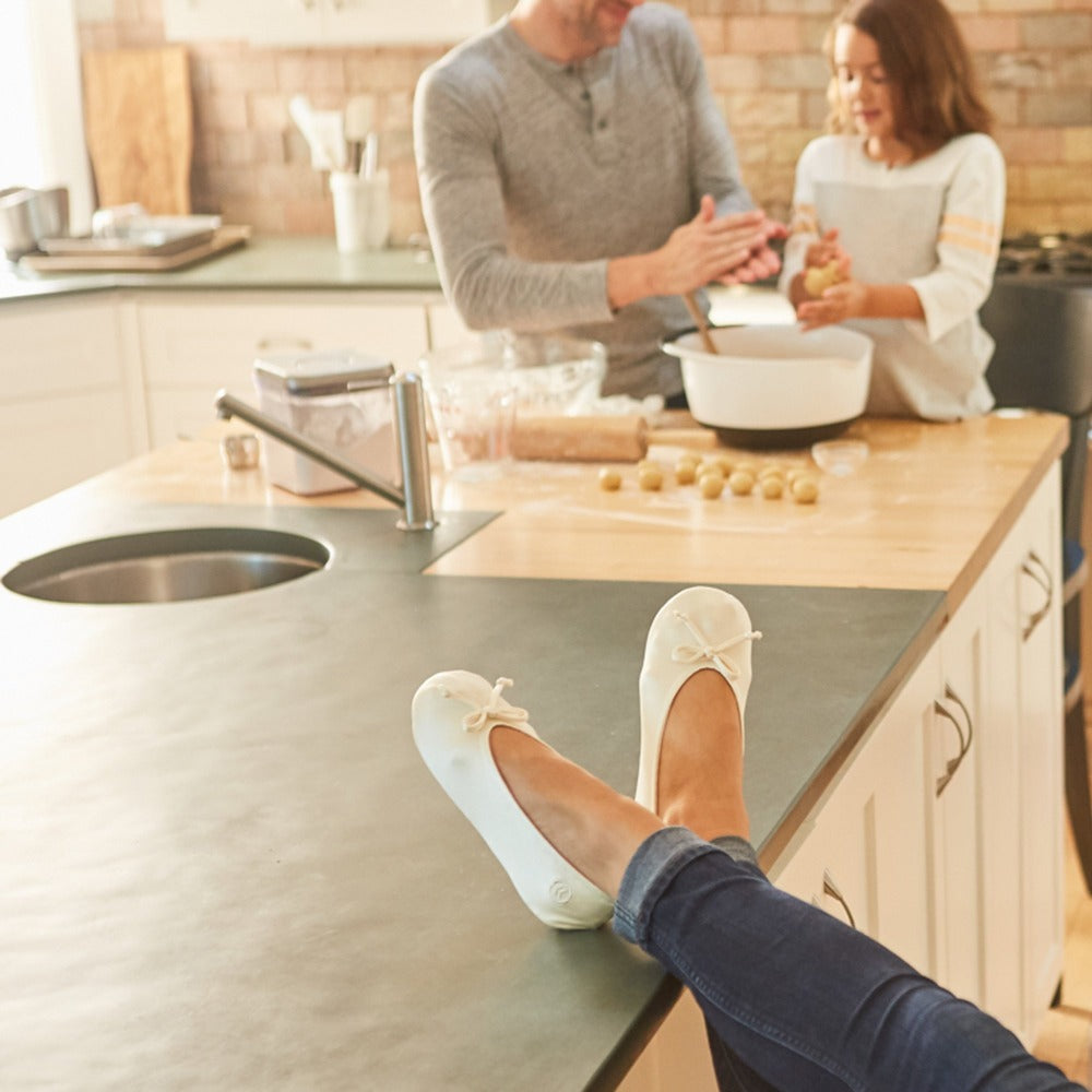 Women's Satin Ballerina Slippers with Satin Bow in White on Model with her feet up on the kitchen counter with man and child making cookies in the background