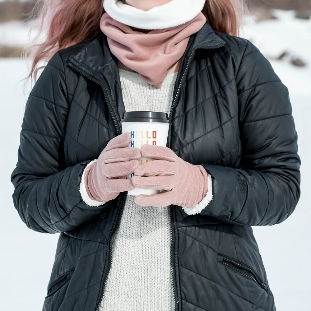 womens stretch fleece glove in winter blossom on figure. Model is holding a reusable coffee cup and standing in the snow