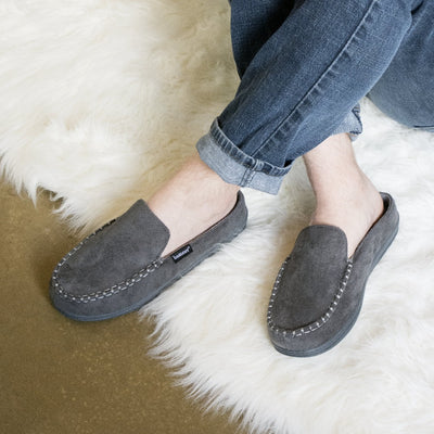 Men's Microsuede Titus Hoodback Slippers in Ash Grey on figure with legs crossed on a fluffy white rug