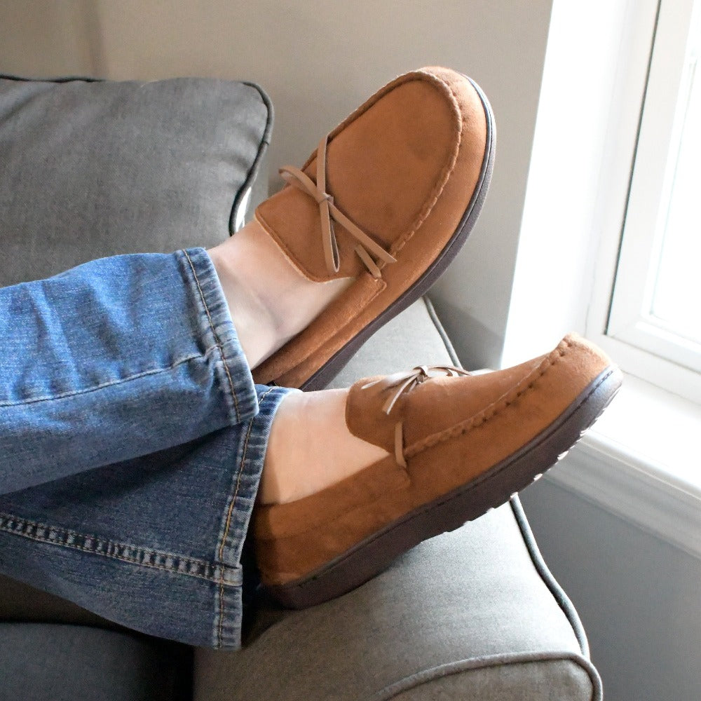 Men's Microsuede Nigel Moccasin Slippers in Cognac on figure. Model lounging with their feet on the arm rest of a chair