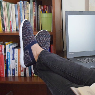 Woman working from home wearing Zenz harmony in navy with her feet up by her computer