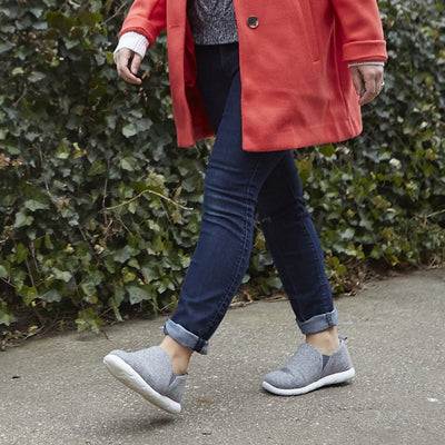 Woman walking on asphalt wearing Zenz Tranquility slipper in heather grey