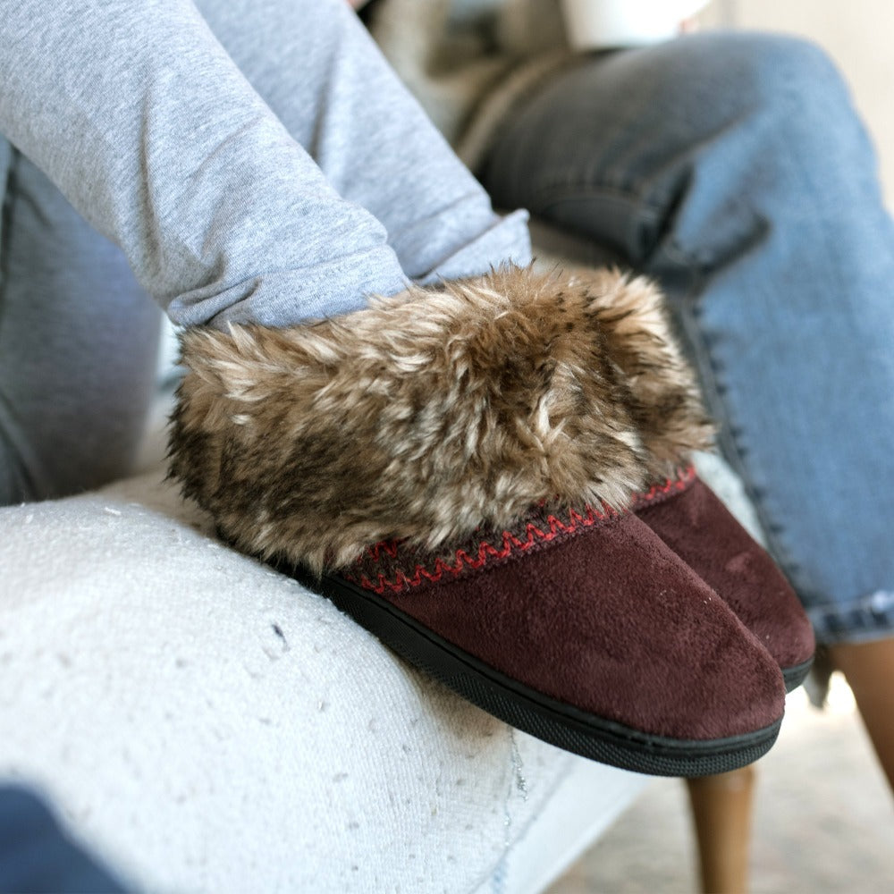 Isotoner Girls Wendi Slipper Boot in Henna Maroon on figure with models feet up on the side of couch