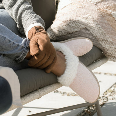Women's Recycled Quilted Bridget Hoodback Slippers in Evening Sand on figure. Model sitting on outdoor seating with her feet on the cushion and a gloved hand resting on her ankle.