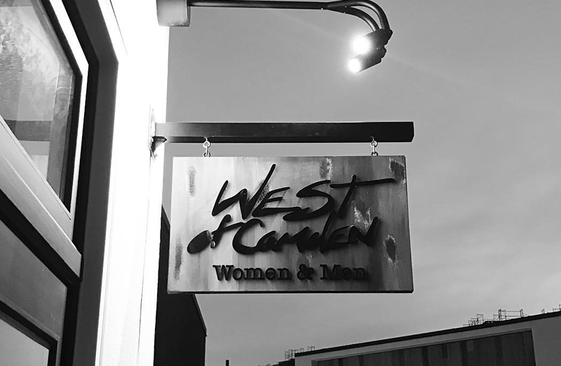West of Camden store blade sign with lights above it, in black an white