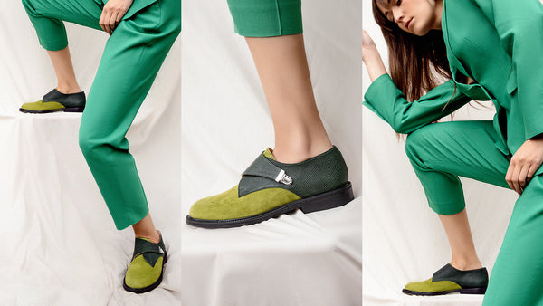 Woman in green suite wearing shoes in green suede and soft leather featuring side monk strap with buckle