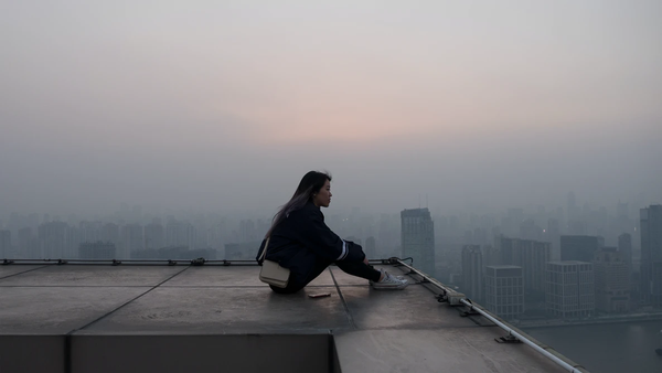 Woman thinking on the edge of a skyscraper