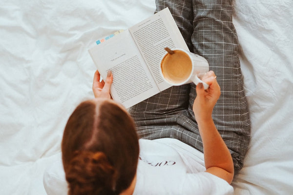 a woman reading a book and drinking coffee