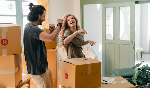 A couple dancing surrounded by moving boxes.