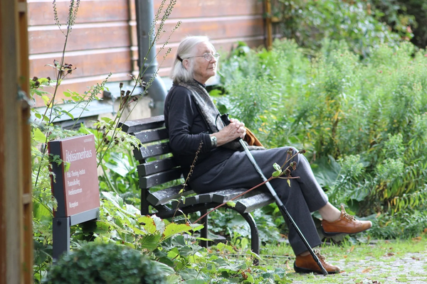 A senior woman with a cane sitting on a bench outside