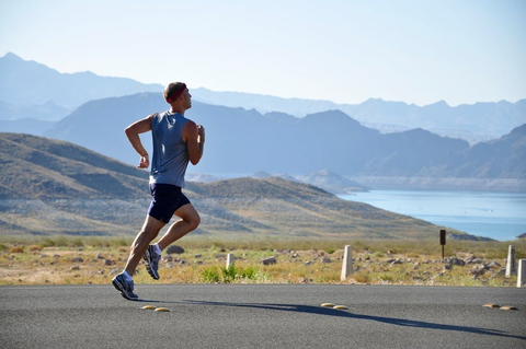 A man running down the road for exercise with mountains in the background.