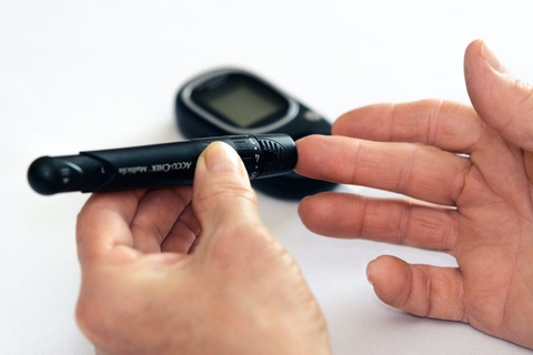 A person with diabetes pricking their finger to test their blood sugar with a glucometer.