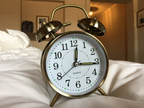 gold clock on bed