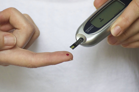 A diabetic person pricking their finger for a blood test with a glucometer.